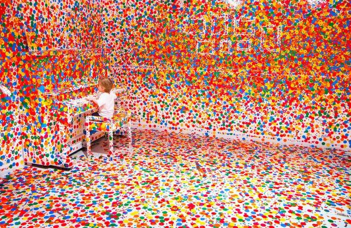 Little kid playing piano in a colorful room