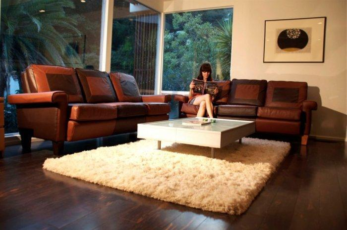 Mid-century modern brown living room with comfortable sofas and white rug