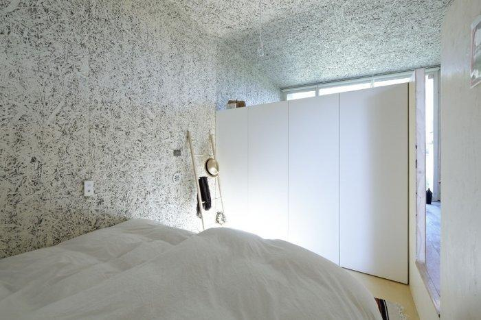 Minimalist bedroom with creative walls in white