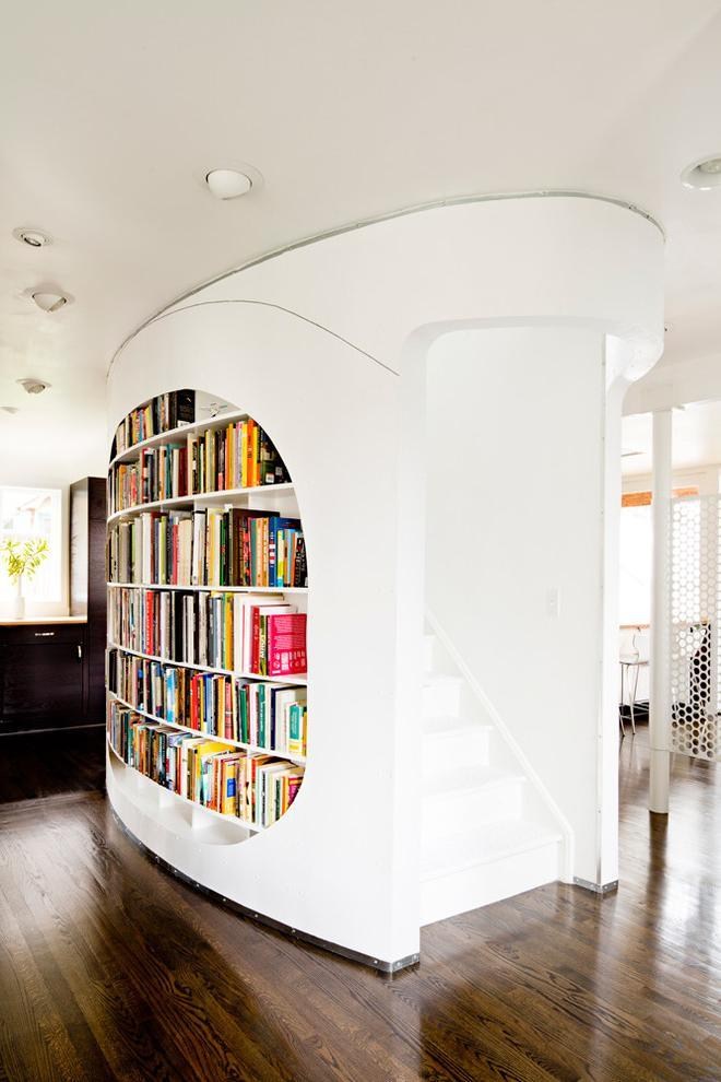 Modern oval bookcase placed in the middle of the house