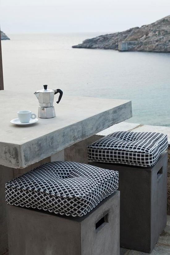 Outdoor concrete table with two creative bar stools