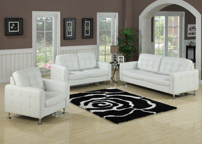 Small white leather sofas placed in a traditional living orom