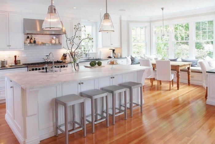 Spacious white kitchen with island and walnut floor laminate