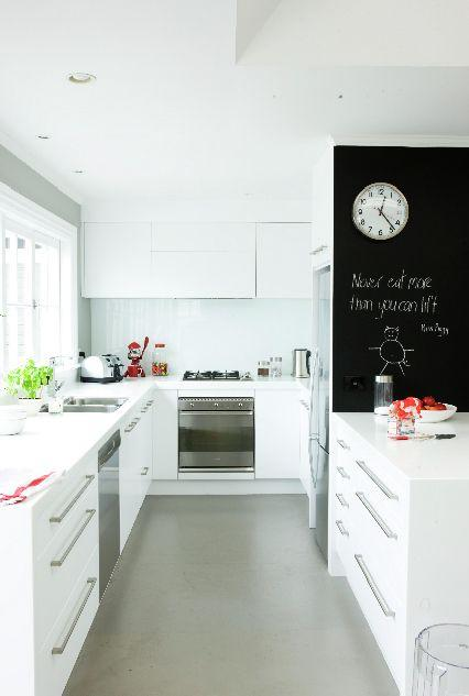 White kitchen design with wall painted with chalkboard paint