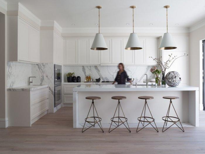 White pendants in a modern kitchen with traditional cabinets