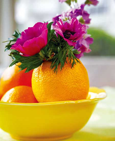 12 - Flowers placed inside a hollowed orange that functions as a vase