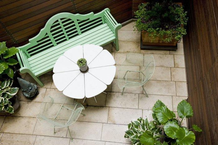 Bench, small coffee table and chairs and flowers in a modern balcony