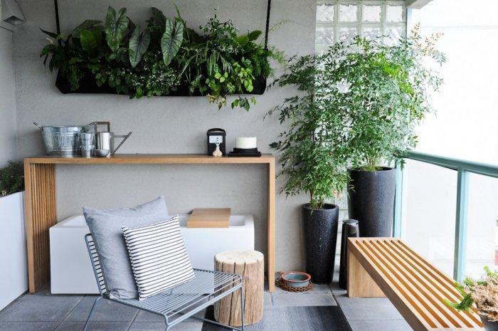 Green plants and high flower pots in a small balcony