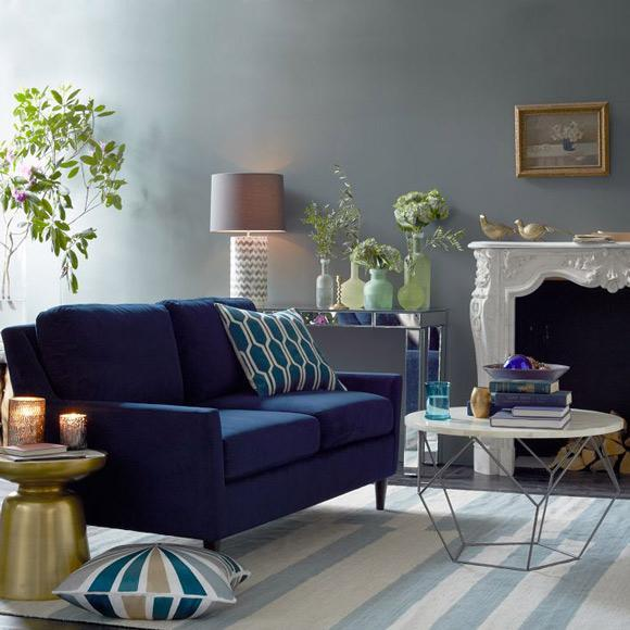 Home decor - blue sofa with natural flowers in the living room