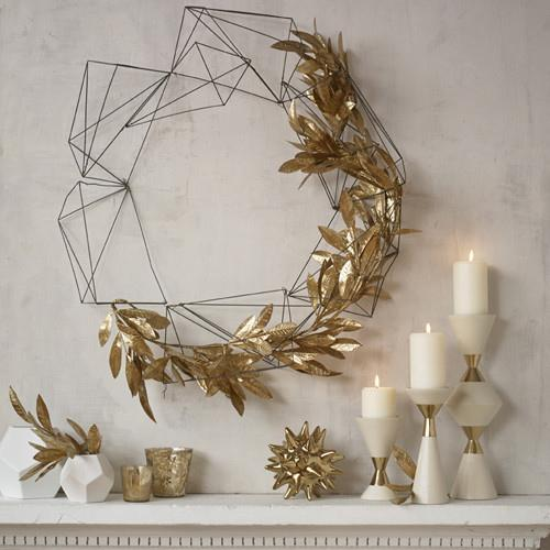 Home decor - golden wreath and candles placed on the wall