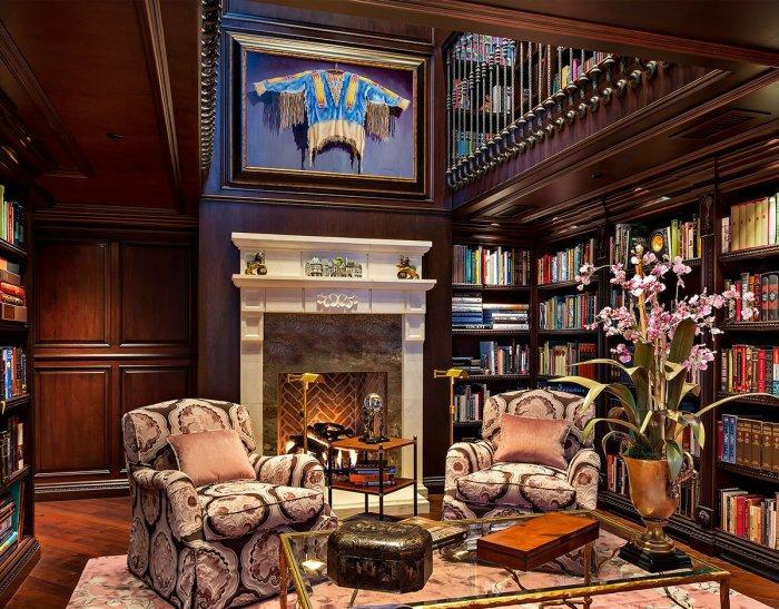 Luxurious traditional home library - with wood shelves and club armchairs