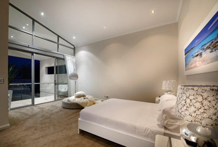 Luxurious white bedroom with view towards the nearby ocean
