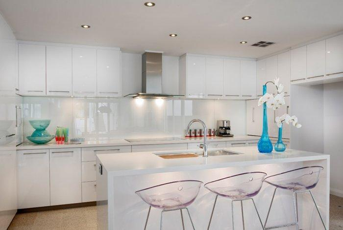 Modern white kitchen with polished island in white
