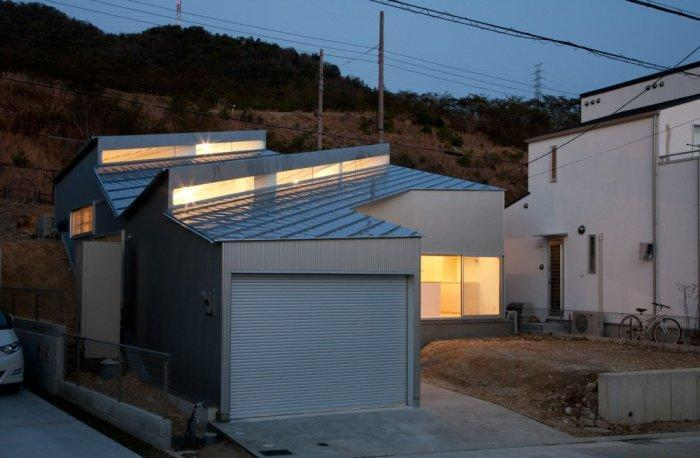 Small minimalist house at night located on a hill