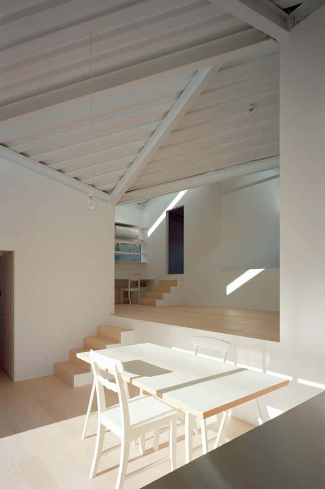 Small minimalist house with dining area consisting of small table and chairs