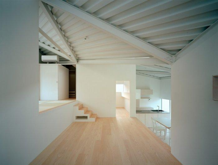 Small minimalist house with wooden flooring and white walls
