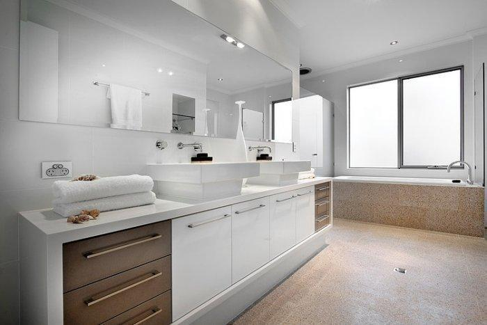 Spacious white bathroom with modern faucets and mirror