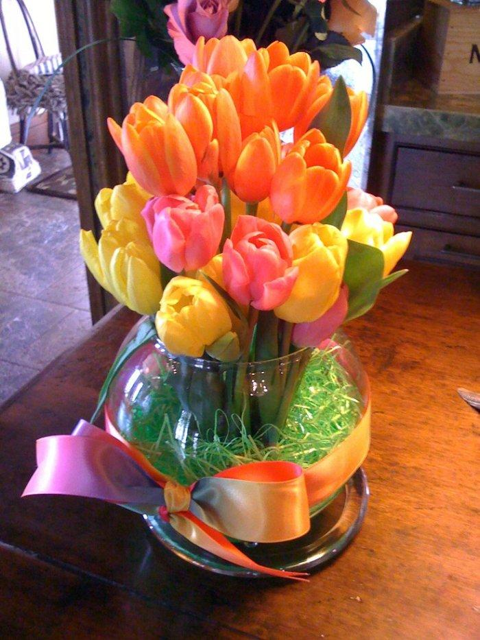 Spring tulips - placed in a glass pot with green decorations inside
