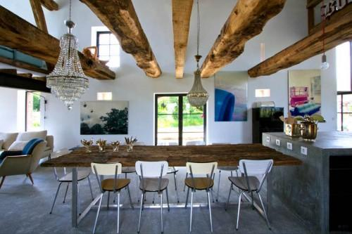 Summer villa - luxurious dining room with rustic table and barn beams above it