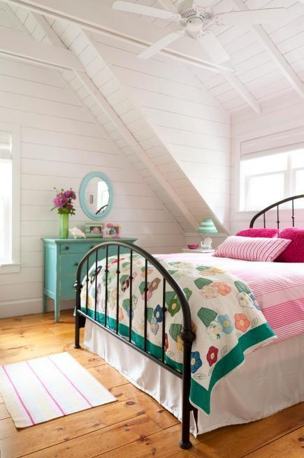 White attic bedroo - with colorful bed sheets