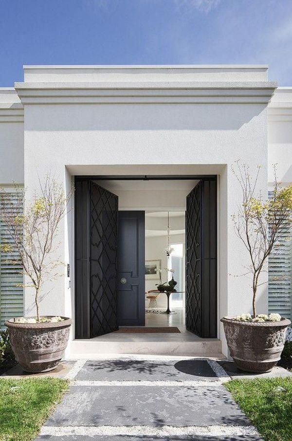 black double front door entering the garden of a luxurious house