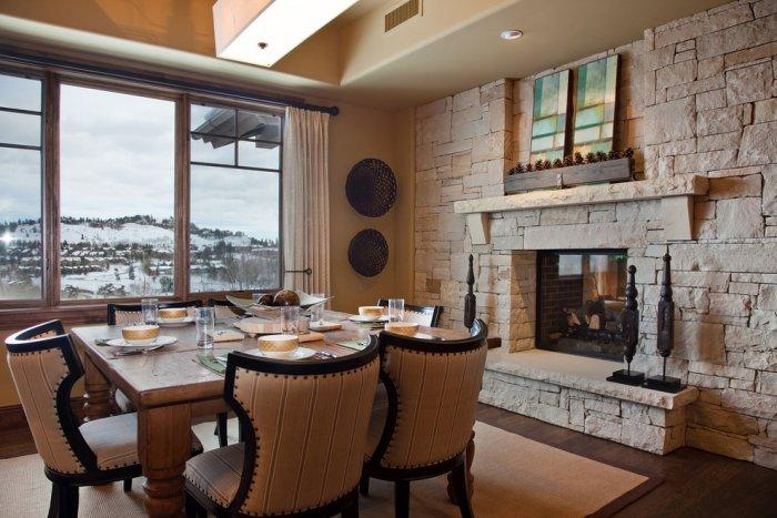 Dining room with stone fireplace inside a mountain house for Dining room fireplace ideas
