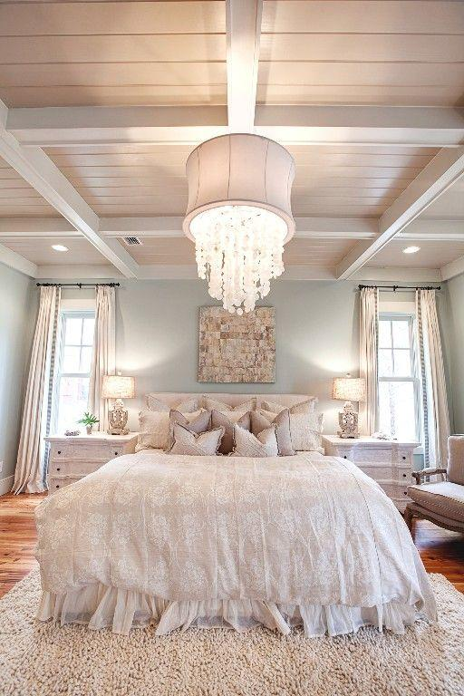 Eclectic white bedroom - with barn beams and crystal chandelier