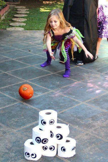 Girl in Halloween costume - playing with a pumpkin