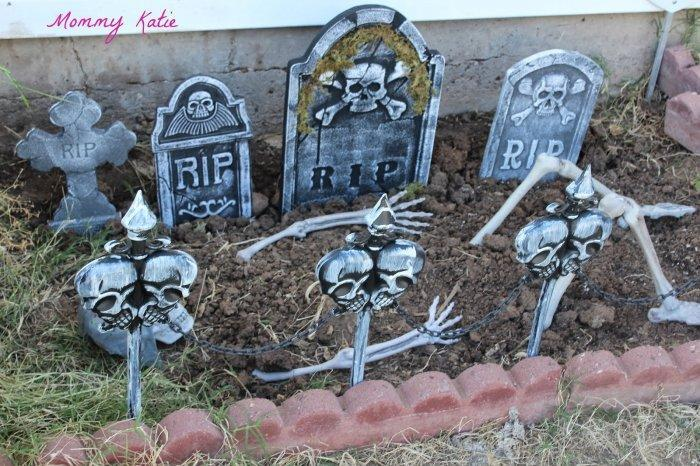 Halloween yard with graves - and skulls in the soil