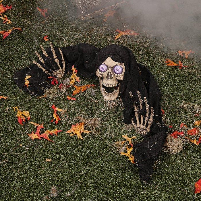 Halloween yard with skeleton - half-burried in the ground