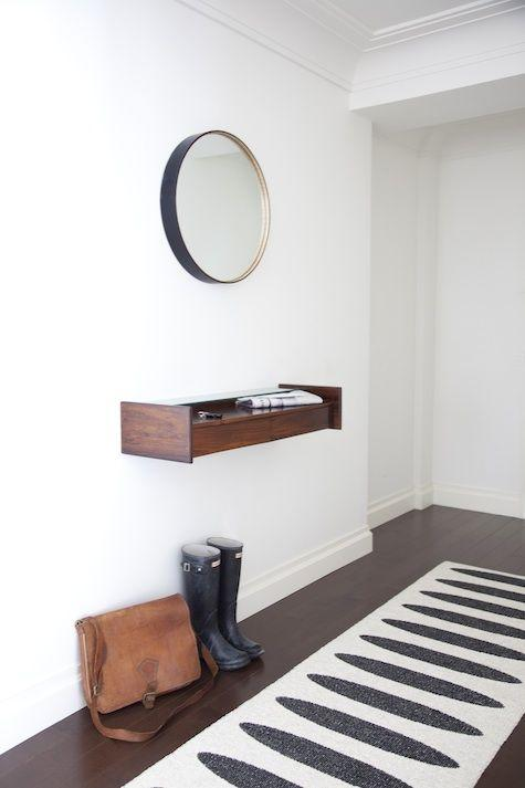 hallway decorative shelf and round mirror above it