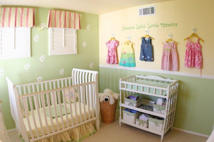 Pale colorful baby room - with small clothes decorating the wall