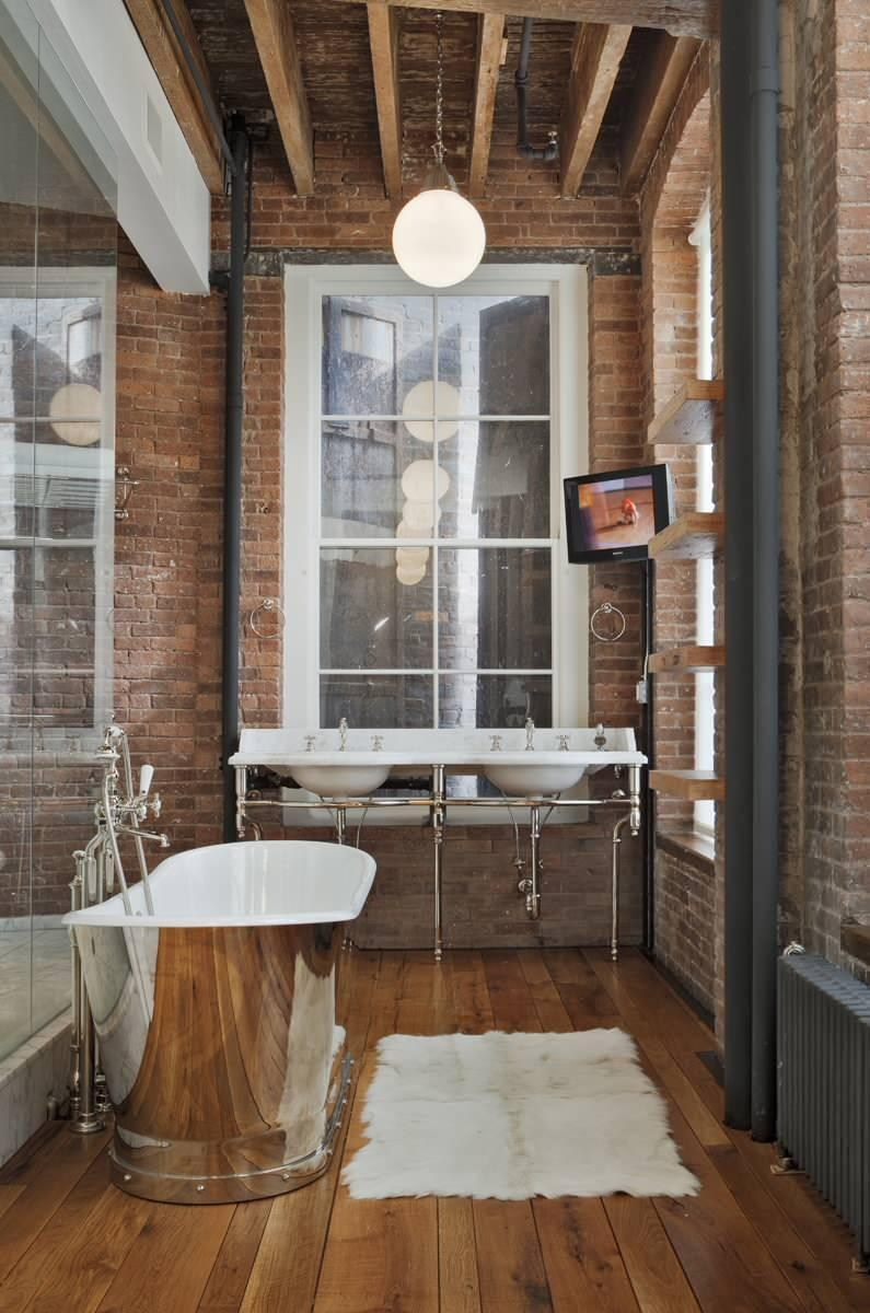 Small loft bathroom - with nickel bathtub and brick wall