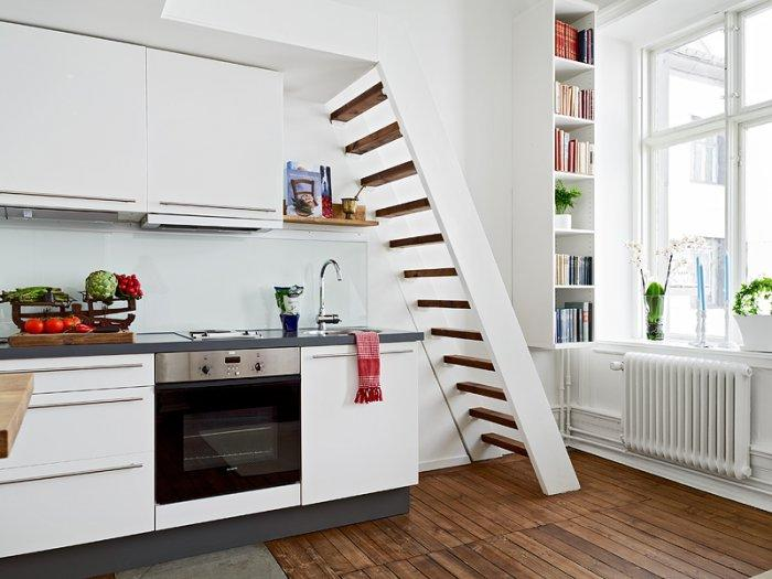 Small white kitchen - with stairs and bed above it