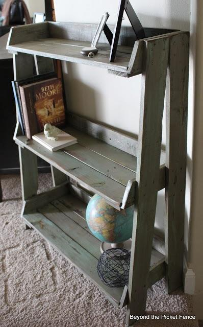 Brown pallet bookshelf - with globe, books and pictures