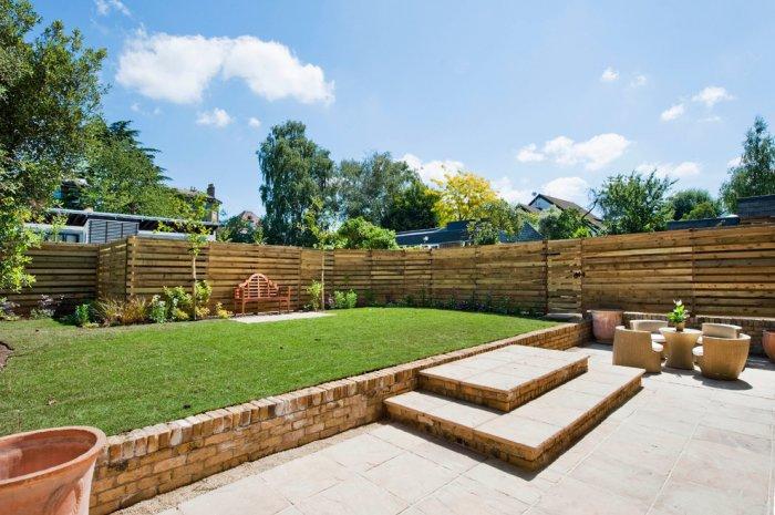 Long pallet fence - in sunny garden