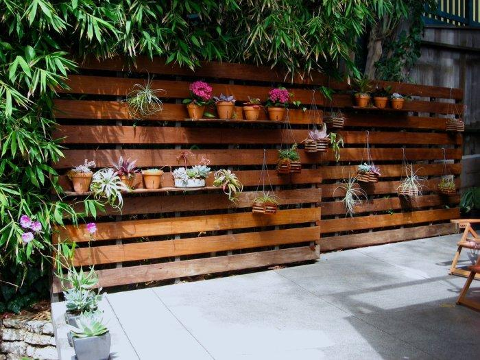 Pallet fence with flowers - and concerete pavement