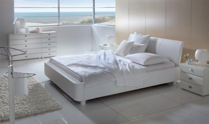 Pure white designer bed - in a minimalist bedroom