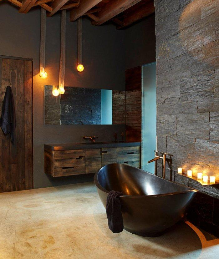 Rustic bathroom with stone wall vintage bathtub and antler chandelier