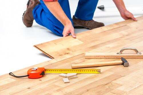 10 Reasons why laminate is better than carpet: Man laying laminate flooring