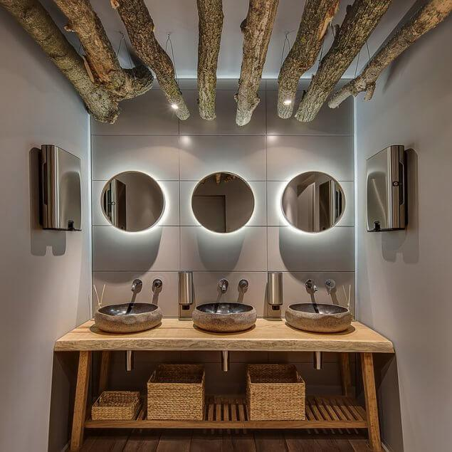 Washroom in a modern style with gray wall and a parquet in the cafe. There are hanging logs with lamps, mirrors with backlight, wooden table with sinks and baskets, soap dispensers, hand dryers.