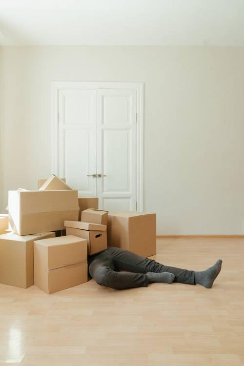 Person in Black Leather Boots Sitting on Brown Cardboard Boxes