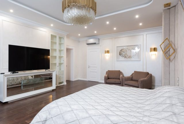 Interior of spacious classic styled bedroom decorated with golden chandelier and lamps