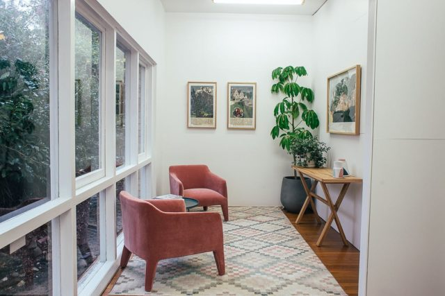 Interior of light hall with windows and armchairs on carpet near table and potted plant with pictures placed on white wall